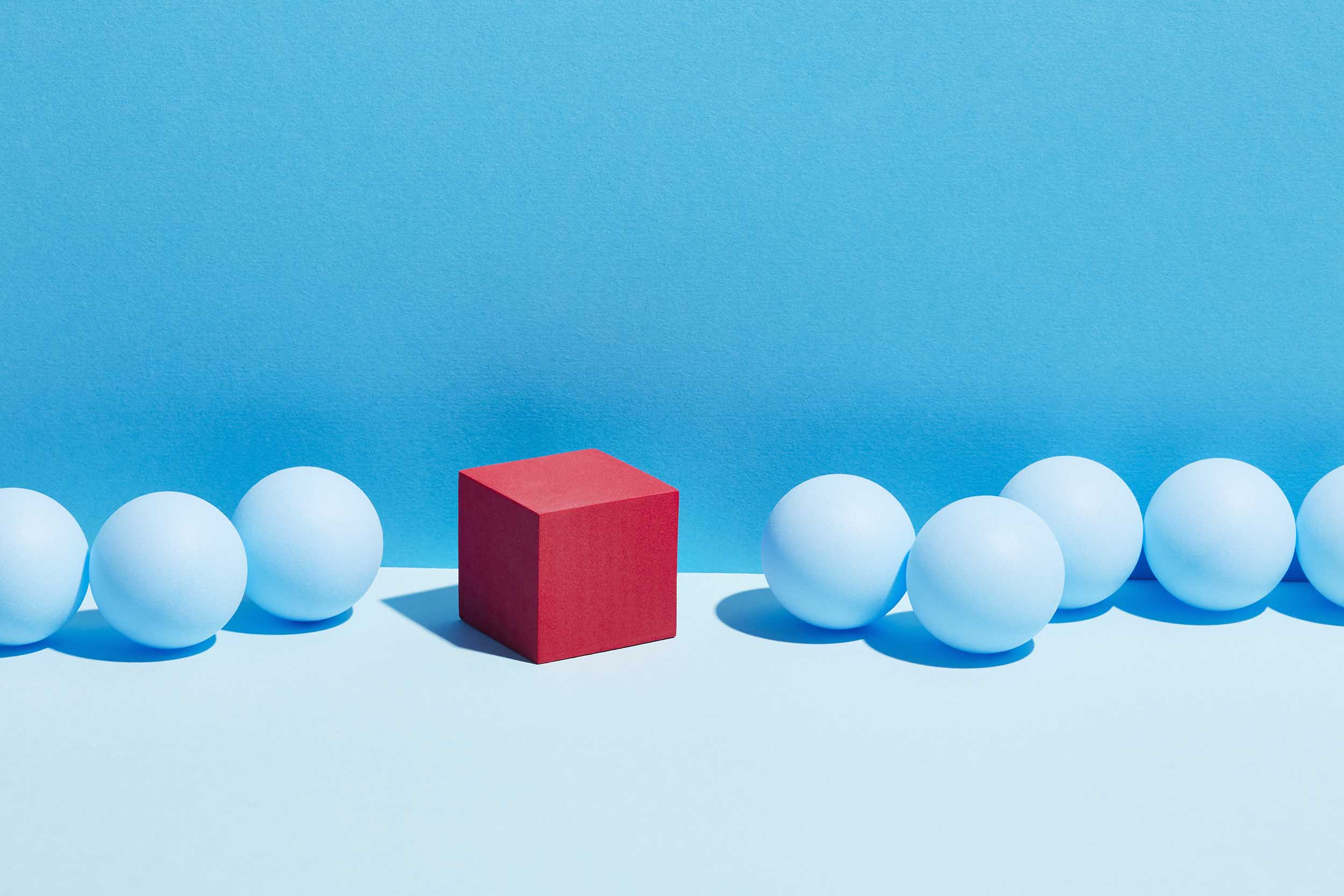 A red cube stands in a row of blue spheres