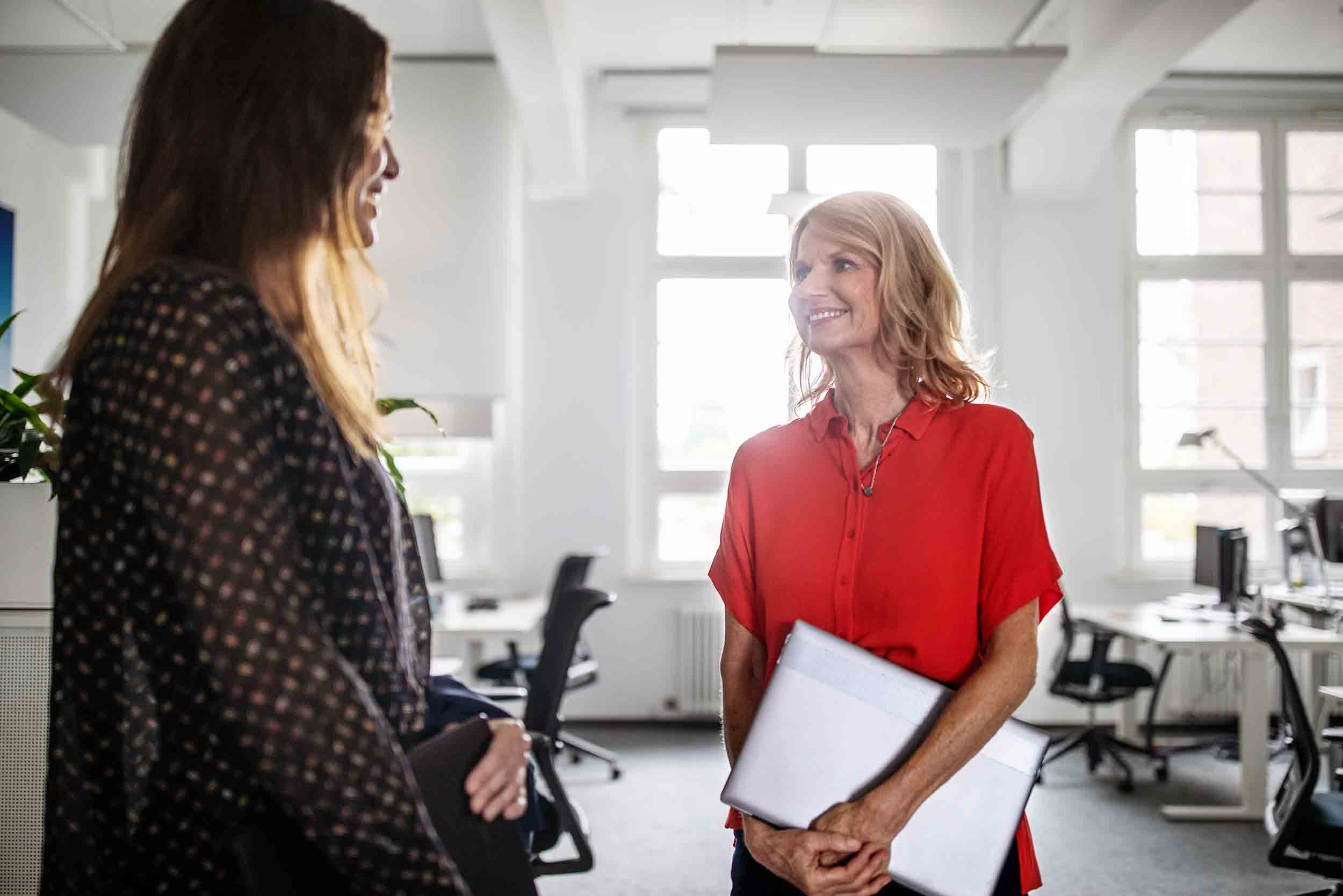 Smiling businesswoman discussing with female colleague while standing in creative office