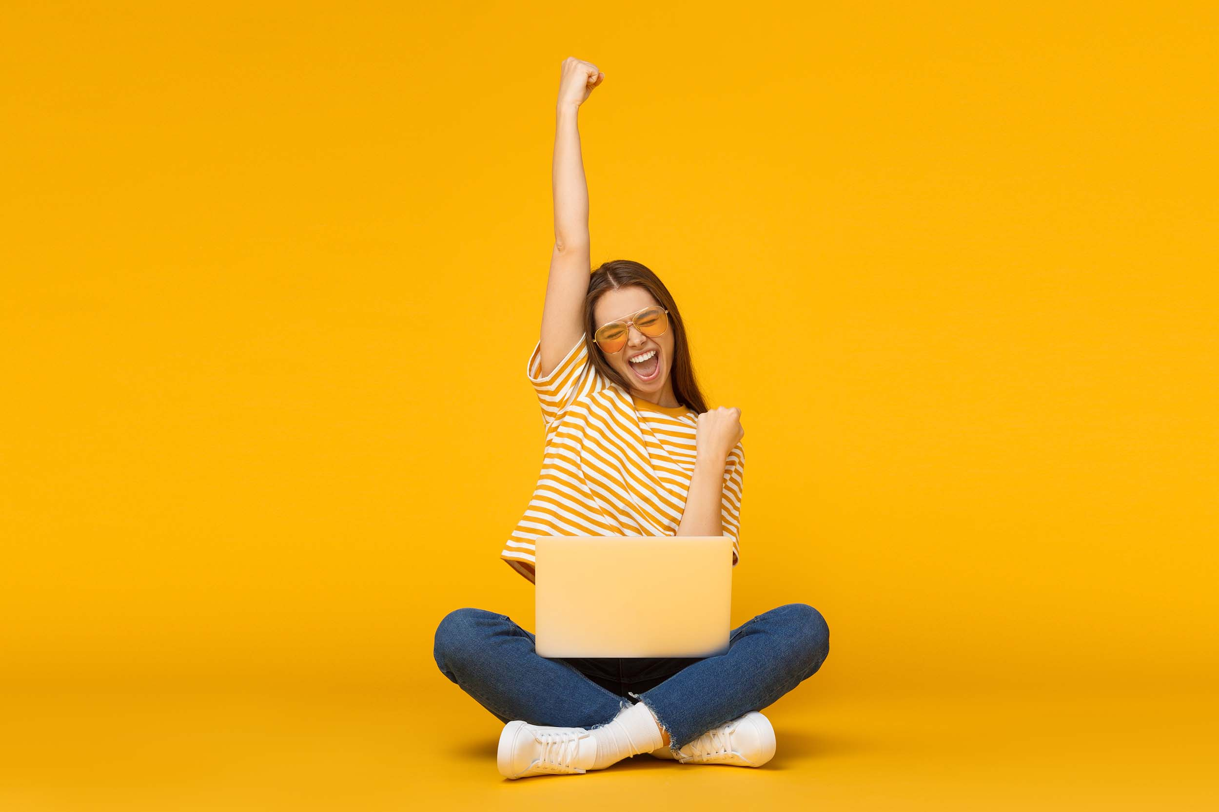 female with laptop isolated on yellow background